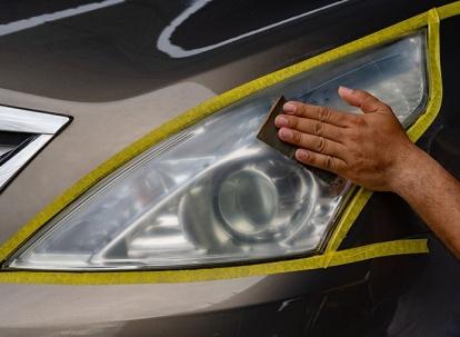 Repairing car headlight, worker hand sanding plastic